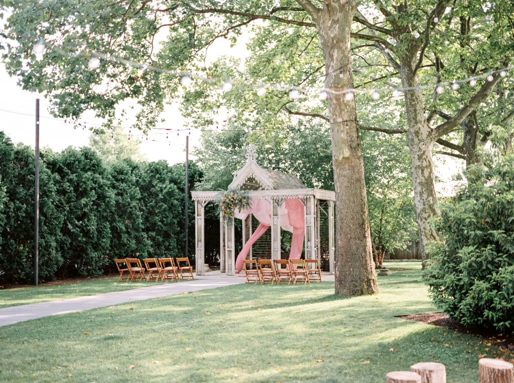 Ceremony space with vibrant flowers at Terrain at Styers taken by Philadelphia Wedding Photographer Matt Genders