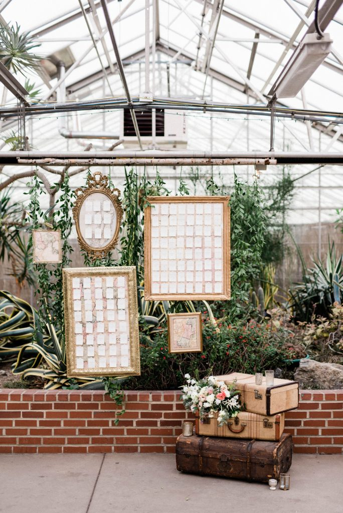 Welcome sign and table assignments on suitcases at the Fairmount Horticulture Center taken by Philadelphia Wedding Photographer Matt Genders Photography