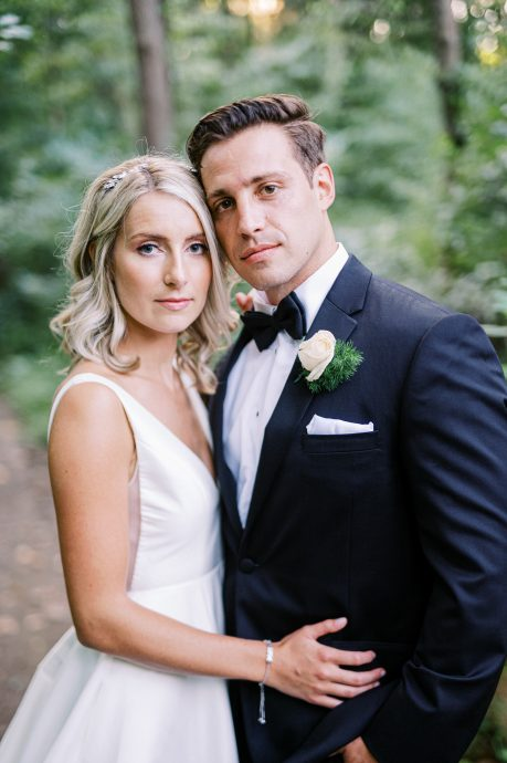 Groom in tuxedo and bride posing in a wooded area at the Old Mill in Rose Valley taken by Philadelphia Wedding Photographer Matt Genders