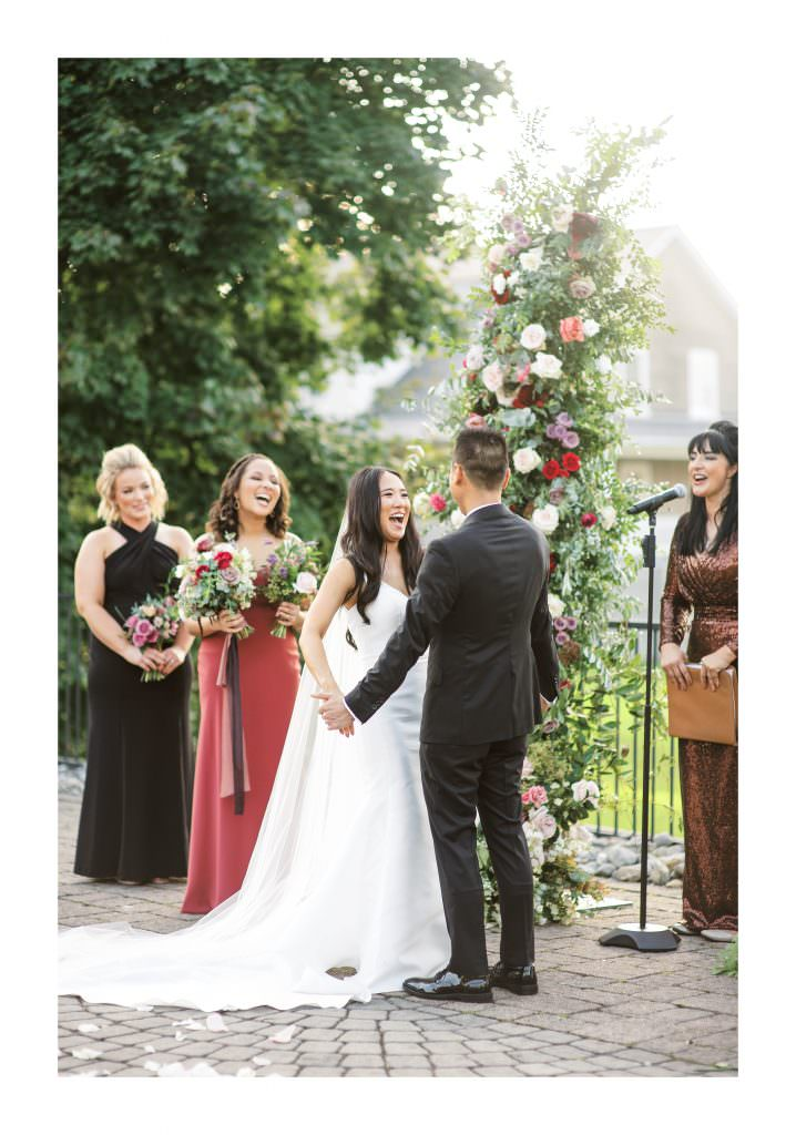 Bride at the alter at Lake House in smiling after first kiss with floral arch by Faye & Renee by Philadelphia Wedding Photographer Matt Genders
