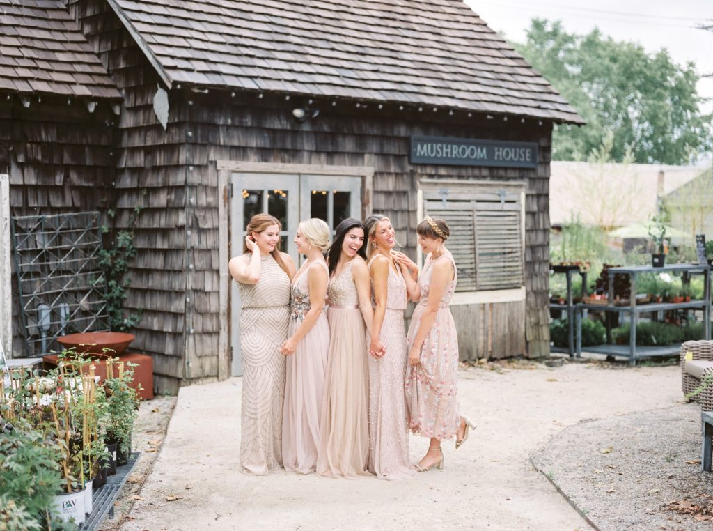 Bridesmaids wearing muted pastel BHLDN dresses laughing together outside the Mushroom House at Terrain at Styers in Glen Mills taken by Philadelphia Wedding Photographer Matt Genders