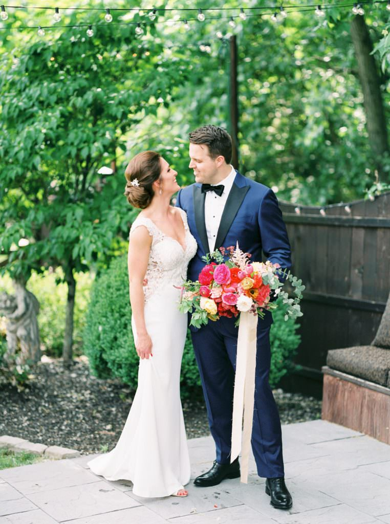 Bride and groom in blue tuxedo holding vibrant bouquet of peonies and roses by A Cottage Gardener by Philadelphia Wedding Photographer Matt Genders