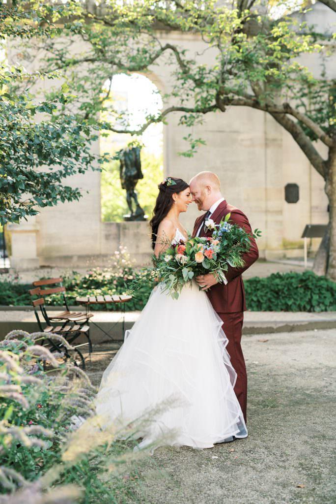 Bride and Groom in maroon suit inside the Rodin Museum garden with Laurel & Elm taken by Philadelphia Wedding Photographer Matt Genders Photography