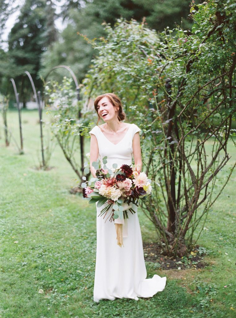 Bride laughing in BHLDN dress holding bouquet by We Are Wildflowers at Glen Foerd Estate taken by Philadelphia Wedding Photographer Matt Genders
