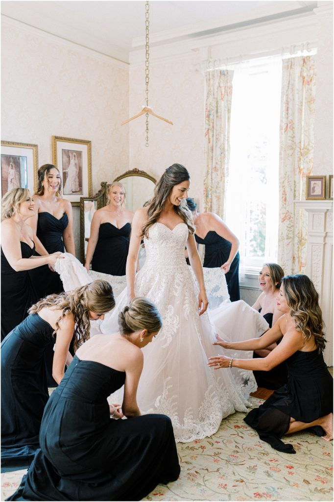 Bridesmaids in black dresses helping the bride get ready at Cairnwood Estate by Philadelphia Wedding Photographer Matt Genders