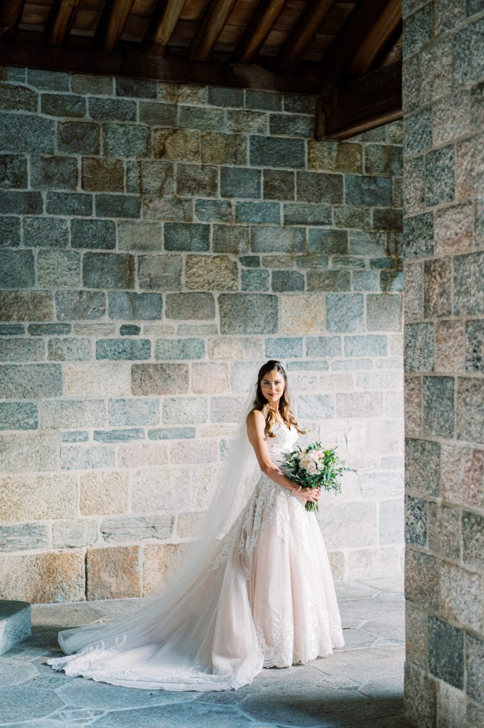 Bride with bouquet in the cloisters at Cairnwood Estate taken by Philadelphia Wedding Photographer Matt Genders Photography