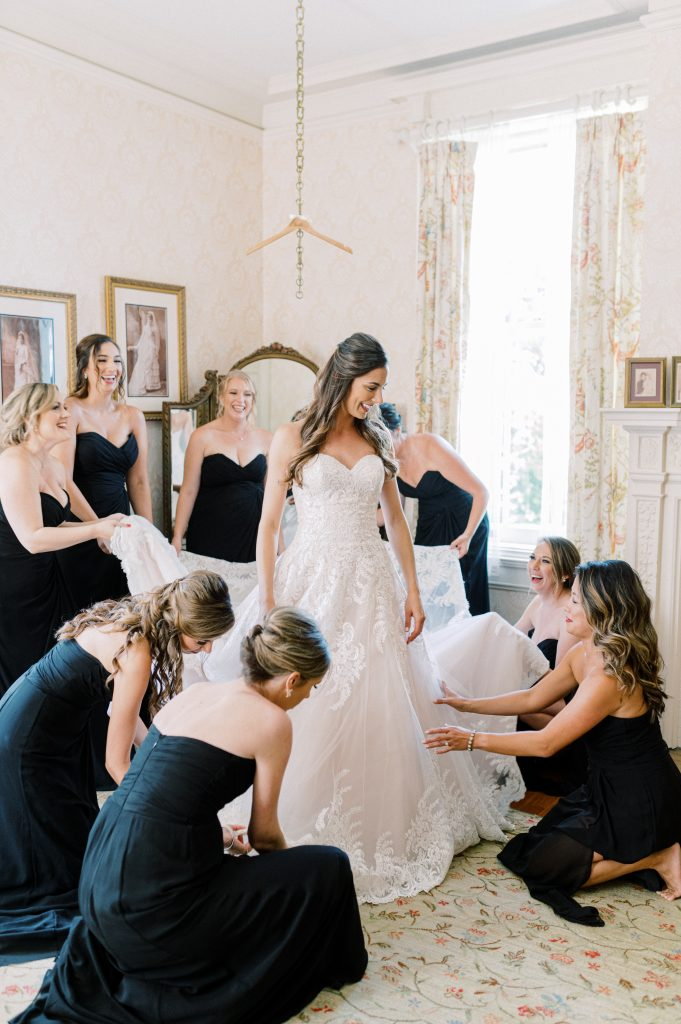 Bride with Bridesmaids putting on dress at Cairnwood Estate taken by Philadelphia Wedding Photographer Matt Genders Photography