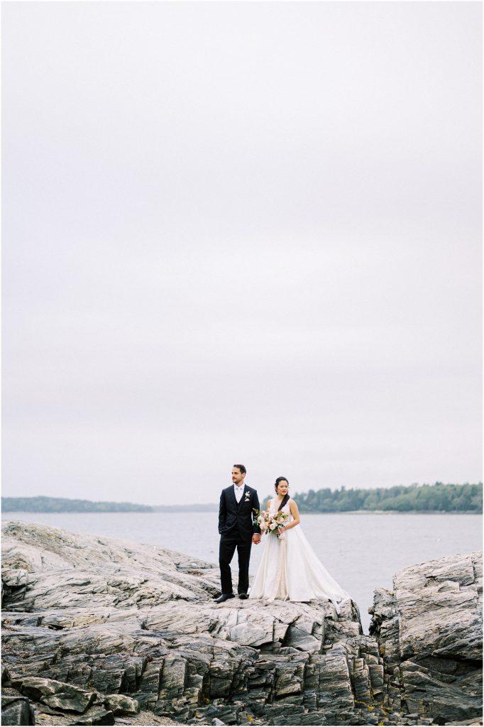 Bride and groom on rocks outside The Historic Harpswell Inn taken by destination wedding photographer Matt Genders
