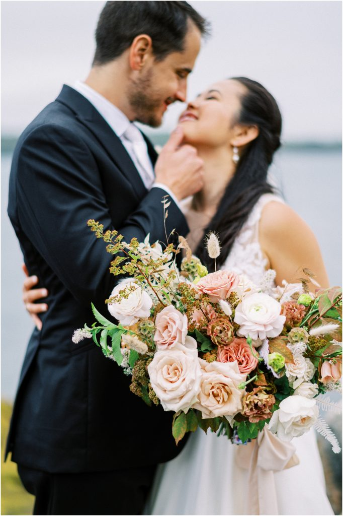 Bride and groom on rocks with mauve bouquet of roses at the Historic Harpswell Inn wedding taken by destination wedding photographer Matt Genders