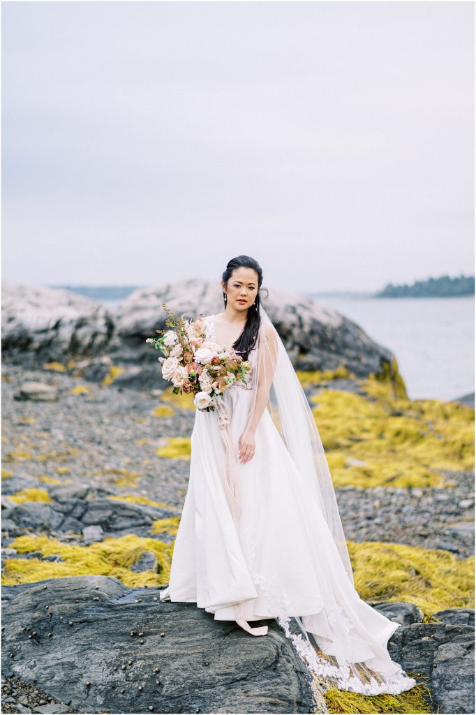 Bride standing on rocks in BHLDN dress with mauve bouquet of roses at the Historic Harpswell Inn wedding by destination wedding photographer Matt Genders