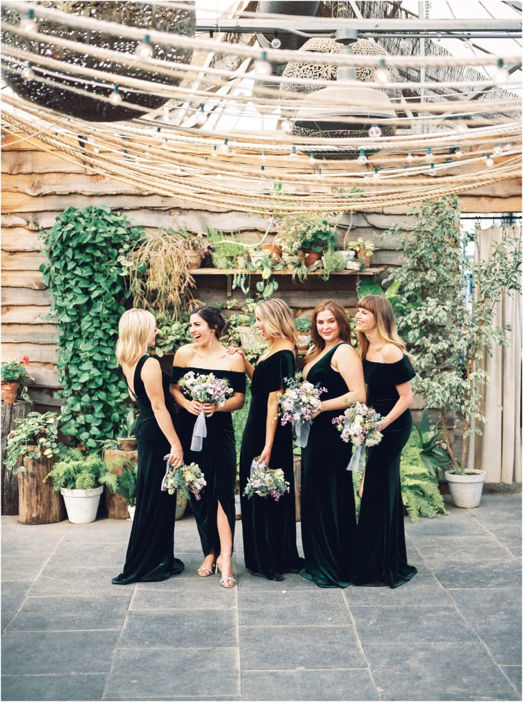 Bridesmaids in BHLDN green velvet dresses inside the Hot House at Terrain at Styers taken by Philadelphia Wedding Photographer Matt Genders Photography