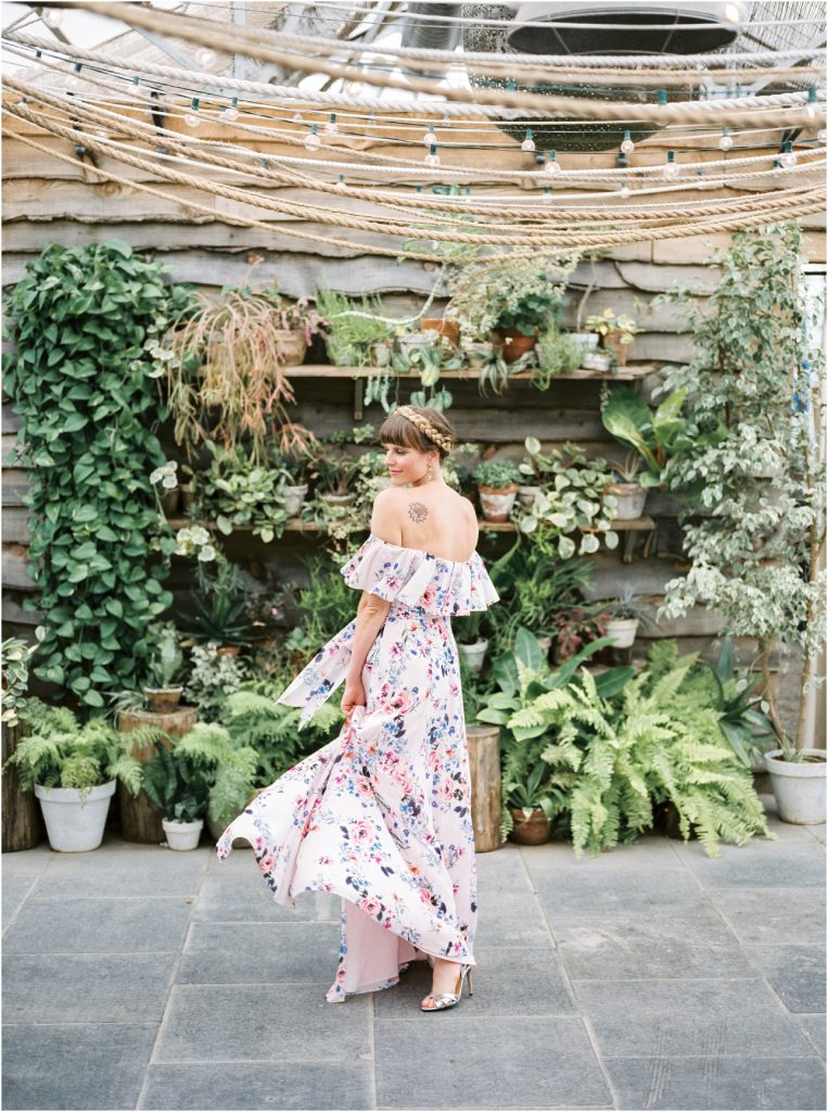 A bridesmaid in a floral pink and white strapless dress in the Hot House at a Terrain at Styers wedding taken by Philadelphia Wedding Photographer Matt Genders Photography