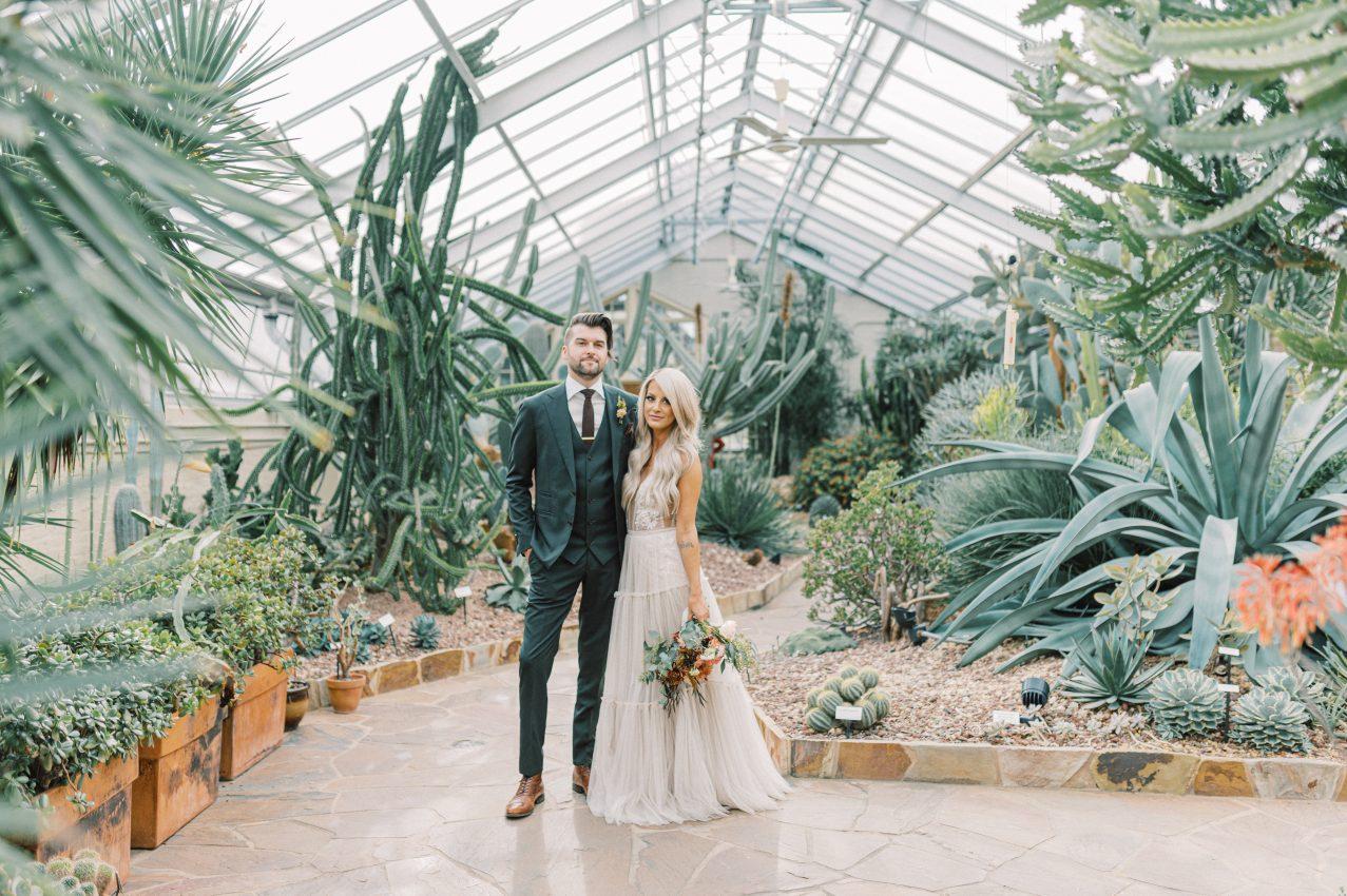 Bride in BHLDN wedding dress holding muted bouquet next to groom in green suit in a greenhouse in Baltimore taken by Philadelphia Wedding Photographer Matt Genders