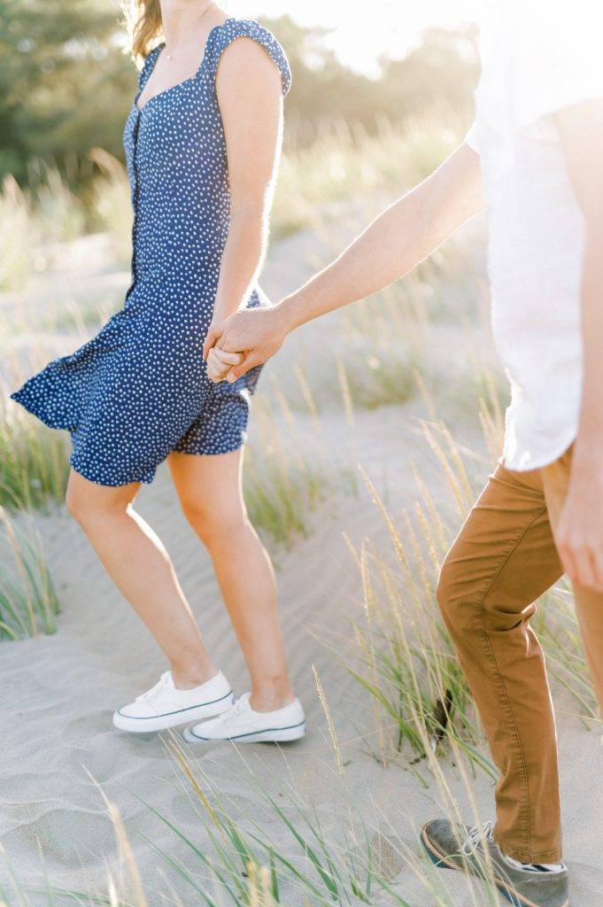 Couple holding hands on sand dunes taken at Rehoboth Beach by Philadelphia Wedding Photographer Matt Genders Photography