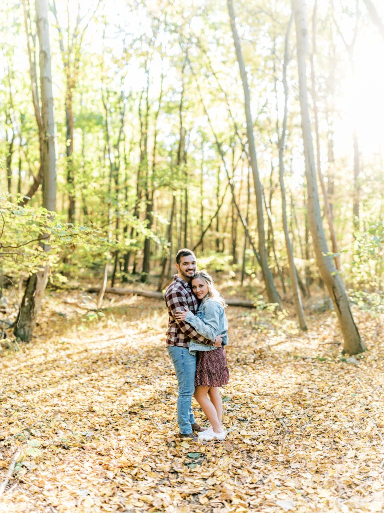 Bride in denim jacket and groom in flannel in the woods embracing at Hawk Mountain Sanctuary taken by Philadelphia Wedding Photographer Matt Genders Photography