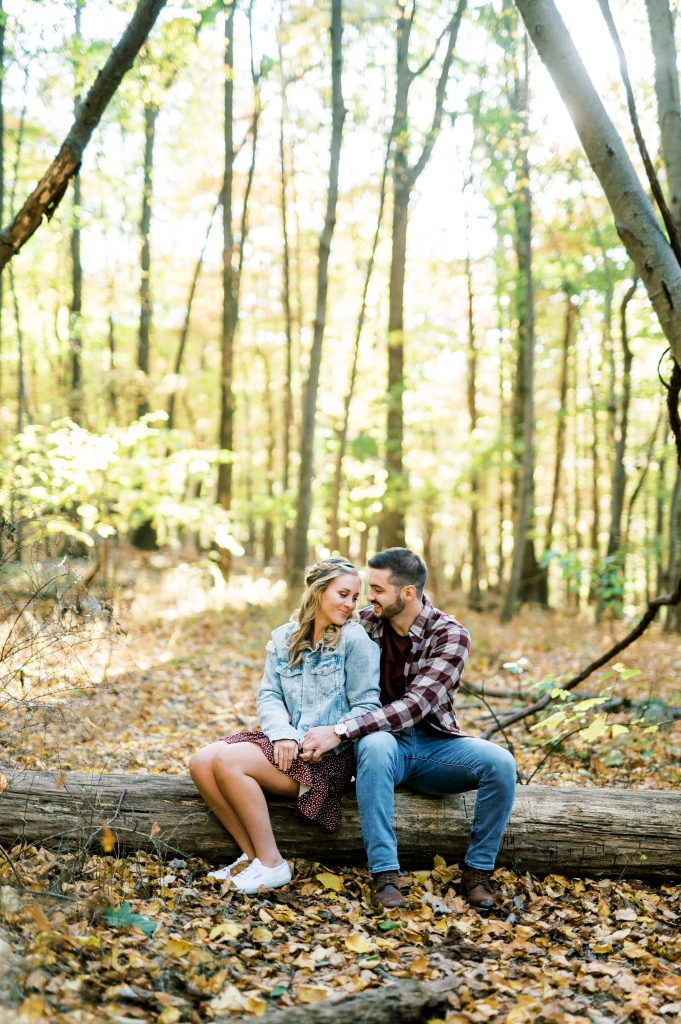 Bride in denim jacket and groom in flannel sitting on a log in the woods at Hawk Mountain Sanctuary taken by Philadelphia Wedding Photographer Matt Genders Photography