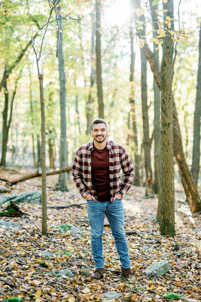 Groom in flannel sitting on a log in the woods at Hawk Mountain Sanctuary taken by Philadelphia Wedding Photographer Matt Genders Photography