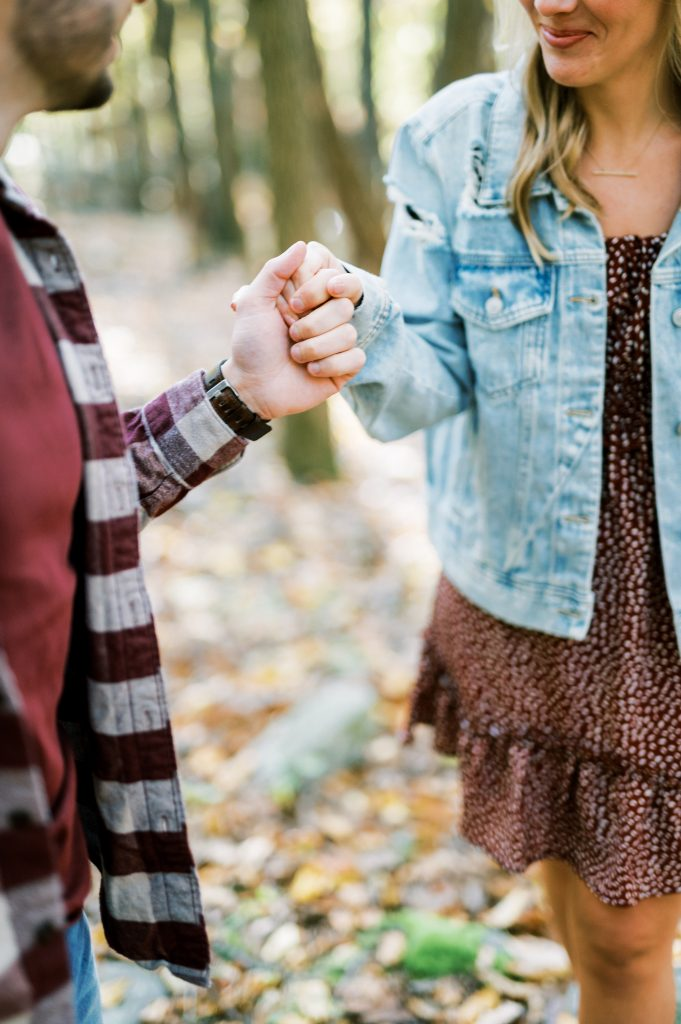 a detail shot of hands of a Bride in denim and floral dress and groom flannel in the woods at Hawk Mountain Sanctuary taken by Philadelphia Wedding Photographer Matt Genders Photography