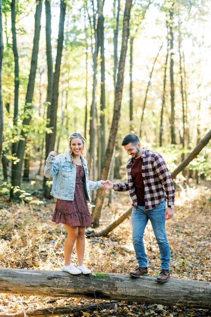 Bride in denim and floral dress and groom flannel holding hands and walking in the woods at Hawk Mountain Sanctuary taken by Philadelphia Wedding Photographer Matt Genders Photography