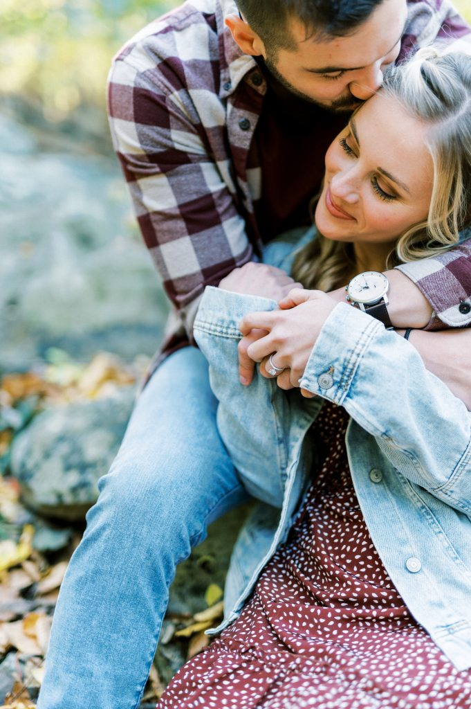 Bride in denim and maroon floral dress and groom flannel sitting on a rock and smiling at Hawk Mountain Sanctuary taken by Philadelphia Wedding Photographer Matt Genders Photography