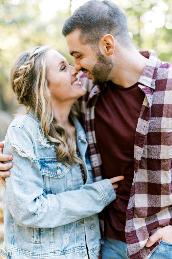 Bride in denim and maroon floral dress and groom flannel touching noses and smiling at Hawk Mountain Sanctuary taken by Philadelphia Wedding Photographer Matt Genders Photography