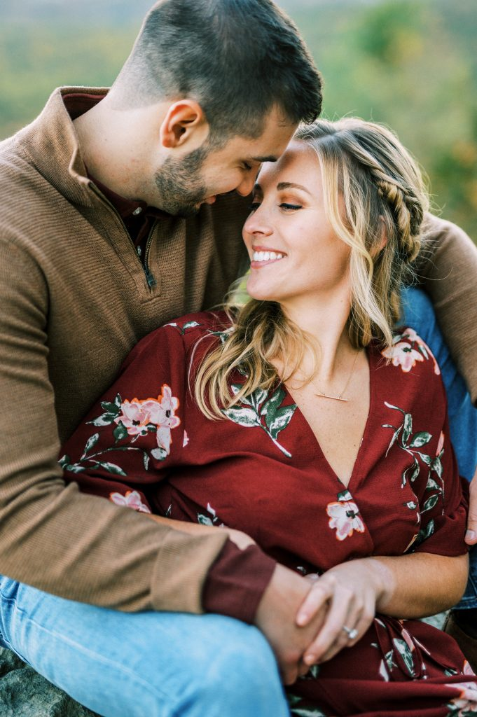 Bride in maroon floral dress and groom in tan sweater and jeans at sunset at Hawk Mountain Sanctuary taken by Philadelphia Wedding Photographer Matt Genders Photography