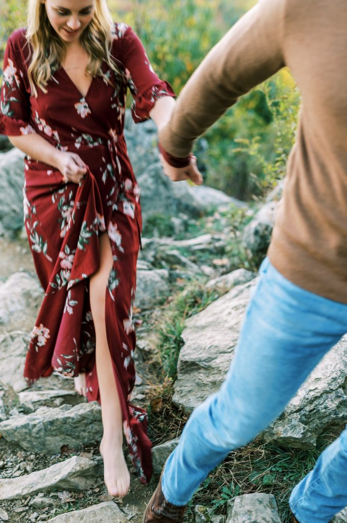 Bride in maroon floral dress and groom in tan sweater and jeans walking on the rocks at Hawk Mountain Sanctuary taken by Philadelphia Wedding Photographer Matt Genders Photography