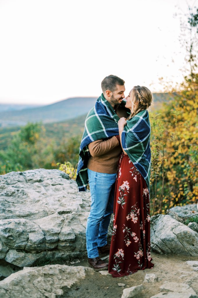 Bride in maroon floral dress and groom in tan sweater and jeans embracing with a flannel blanket at Hawk Mountain Sanctuary taken by Philadelphia Wedding Photographer Matt Genders Photography