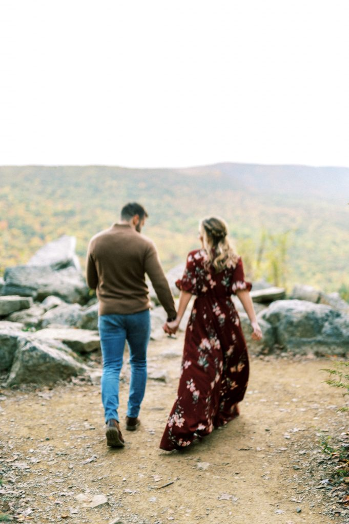 Bride in maroon floral dress and groom in tan sweater and jeans at Hawk Mountain Sanctuary taken by Philadelphia Wedding Photographer Matt Genders Photography