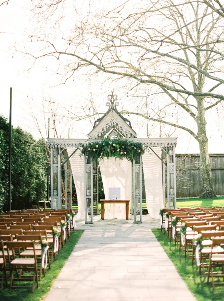 A bohemian alter with green florals and white linens at a wedding at Terrain at Styers taken by Philadelphia Wedding Photographer Matt Genders