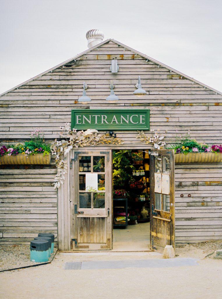 "A green sign saying ""Entrance"" during a Terrain at Styers wedding taken by Philadelphia Wedding Photographer Matt Genders"