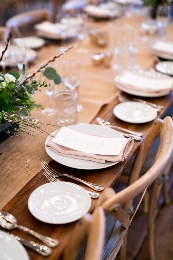 A close up on plates of a reception set up with white floral bouquets at Terrain at Styers taken by Philadelphia Wedding Photographer Matt Genders Photography