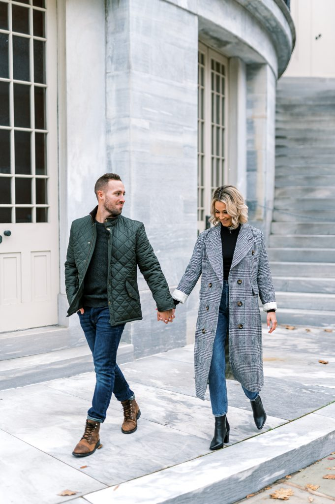 bride in herringbone jacket and black turtleneck holding hands with fiance outside Merchant's Exchange Building in Old City Philadelphia by Philadelphia Wedding Photographer Matt Genders