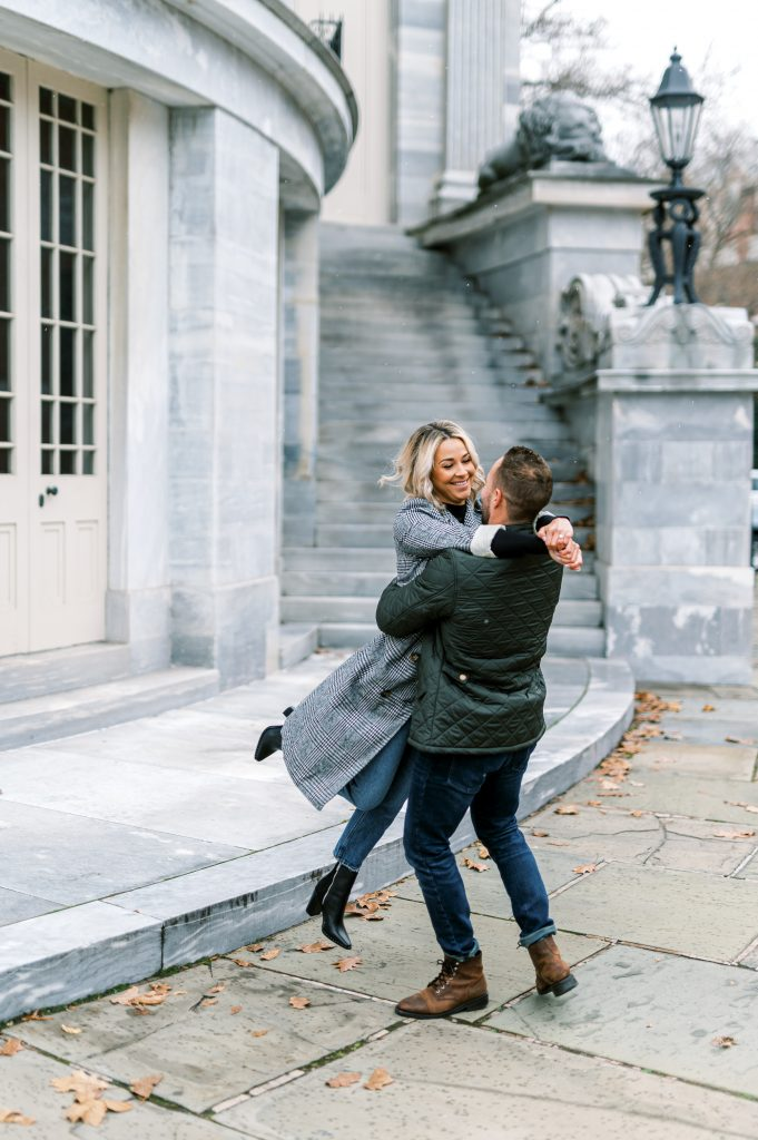 Bride in herringbone jacket and black turtleneck spinning with fiance outside Merchant's Exchange Building in Old City Philadelphia by Philadelphia Wedding Photographer Matt Genders